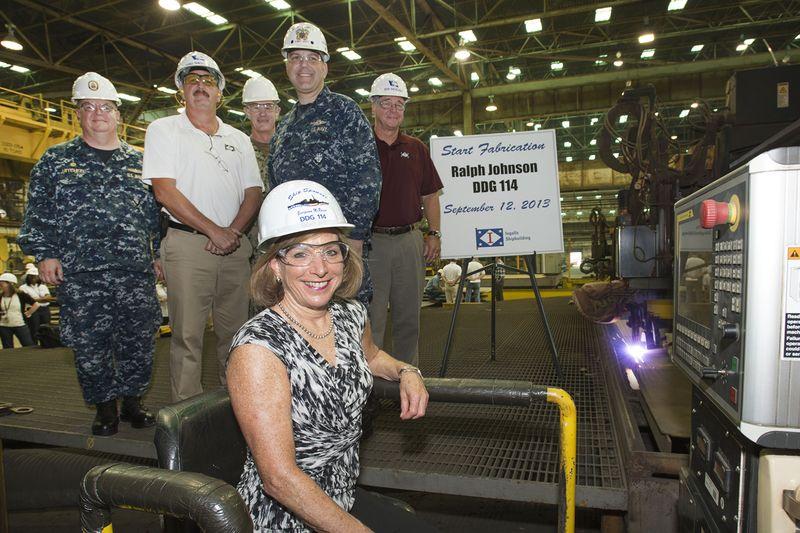Georgeann McRaven, sponsor of Ralph Johnson (DDG 114), starts steel-cutting machine