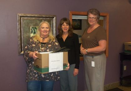 Debra Seidl, operations manager of Golden House, accepts a technology donation from Associated Bank's Angie DeWitt and Annette Gleichner, senior field engineer.