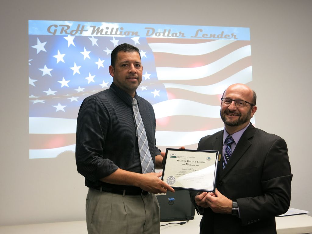 Associated Bank Residential Loan Officer Edgar Bernal (left) accepts the award from USDA Rural Development Acting State Director Dave Schwobe.