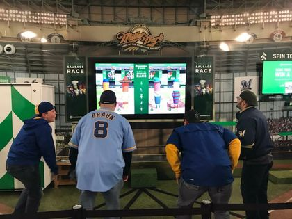 "Fans participate in Associated Bank's exclusive ""virtual sausage race"" as part of the enhanced Miller Park onsite experience"