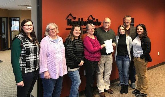 Bill Kopka (fourth from the right) presents the $15,000 donation on behalf of Associated Bank to NeighborWorks Green Bay.