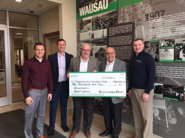 Associated Bank colleagues (from left to right) Jordan Hoerter, Chad Otte, Alfred Nakhla and Andy Shallow, present a check to Romey Wagner (center).