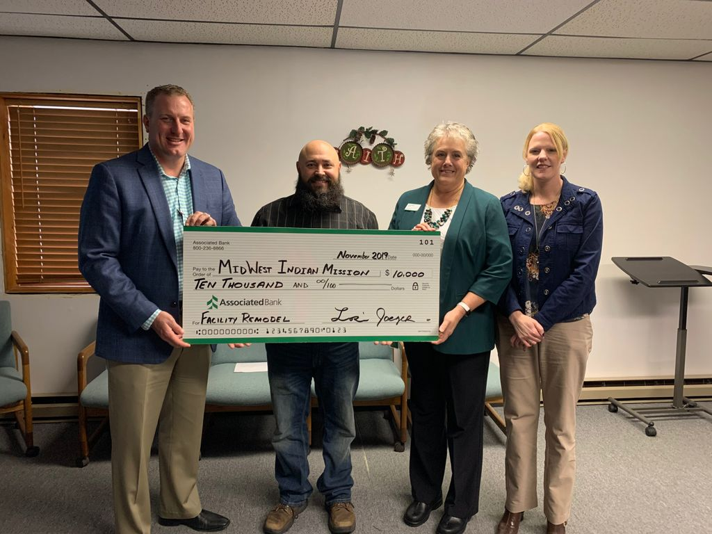 Associated Bank colleagues present a check to Midwest Indian Mission. Pictured from left to right: Brad Kowieski, Micah Dewing, Lori Jaeger and Cindy Bodoh.