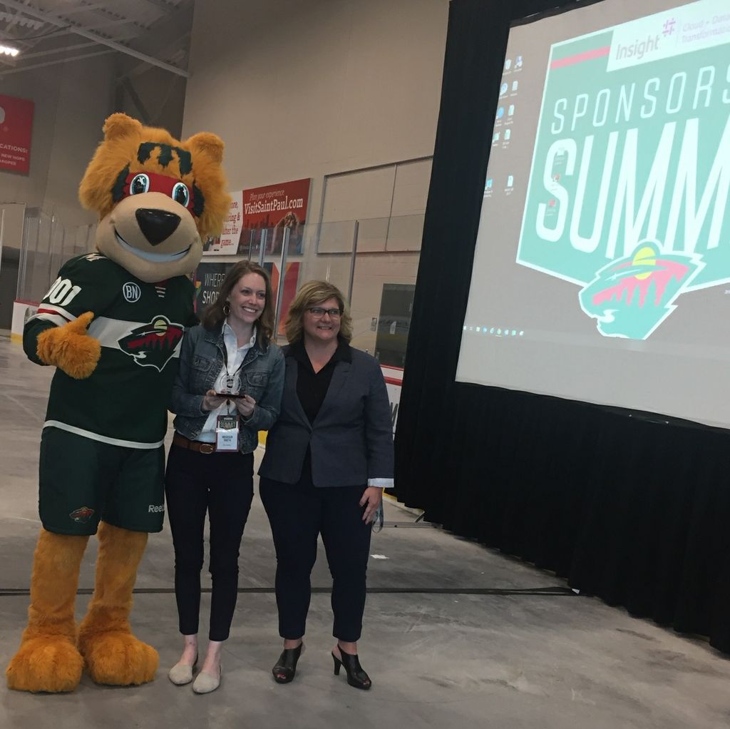 Madison Smith, experiential marketing senior specialist, Associated Bank (center), attended the Minnesota Wild Sponsorship Summit event and accepted the award on the Into the Wild planning team's behalf.