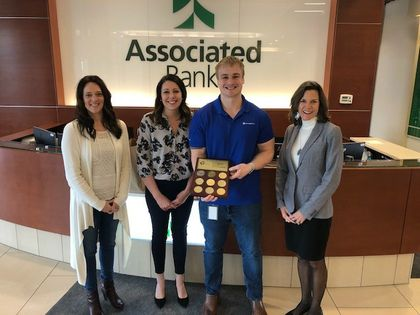 Jane Lowe from the American Heart Association (second from left) presents the award to Melissa Karls, Arthur Valentine and Angie DeWitt of Associated Bank.