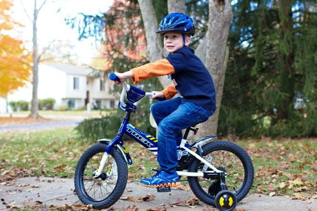 boy with training wheels bike helmet
