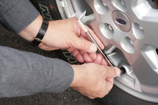 Closeup of hands using tire pressure gauge