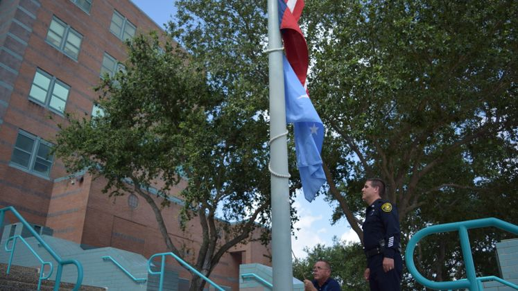 Sr. Officer M. Harrod oversees W. Hand lowering the flags to half mast following the Dallas shooting