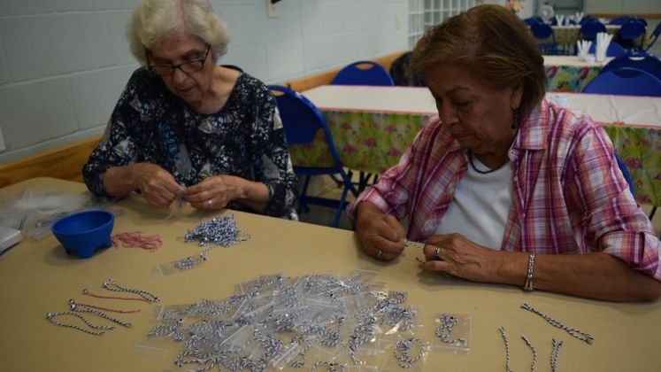 E. Garza and E. Gonzalez making commemorative 911 bracelets at Broadmoor Sr. Ctr.