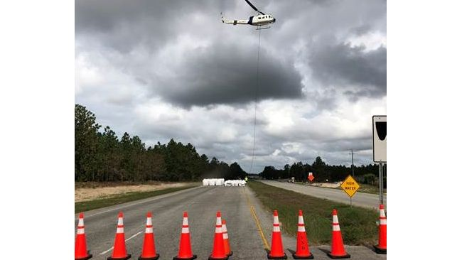 Helicopter operation to left large sandbags and place them inside the breach locations along Sutton Lake dam to help slow the flow of water going out. Photo uploaded Sept. 26, 2018.