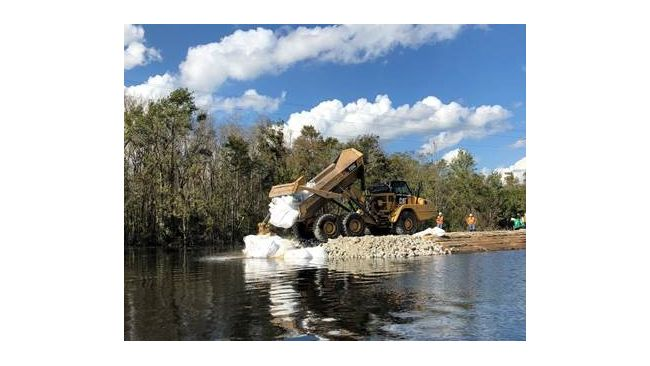 Placing large sandbags and stone to repair the Sutton Lake dam. Photo uploaded Sept. 28, 2018.