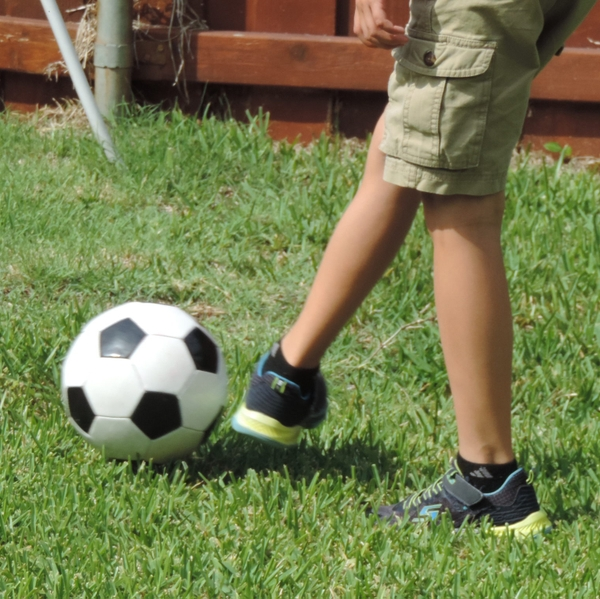 Boy kicks soccer ball