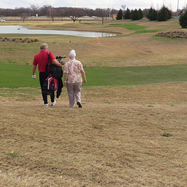 Man+and+woman+walking+on+golf+course