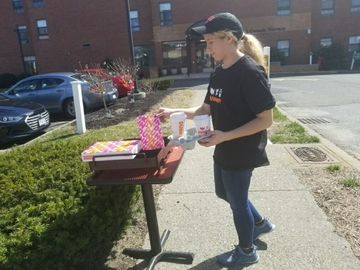 Dunkin' crew member delivering complimentary orders for the elderly