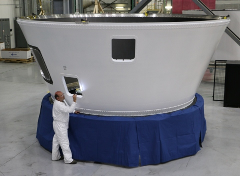 An Orbital ATK employee inspects an Atlas V boat tail, the 500th large composite rocket structure pr ...