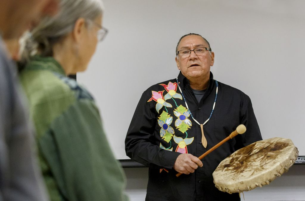 a Native American physician plays hand drum and sings
