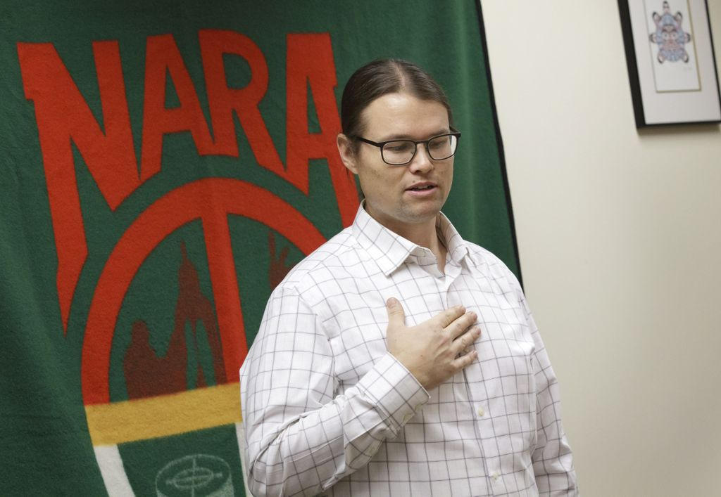 Man wearing glasses looks toward the ground as he gestures near his heart and stands in front of a green patterned wool blanket hanging behind him.
