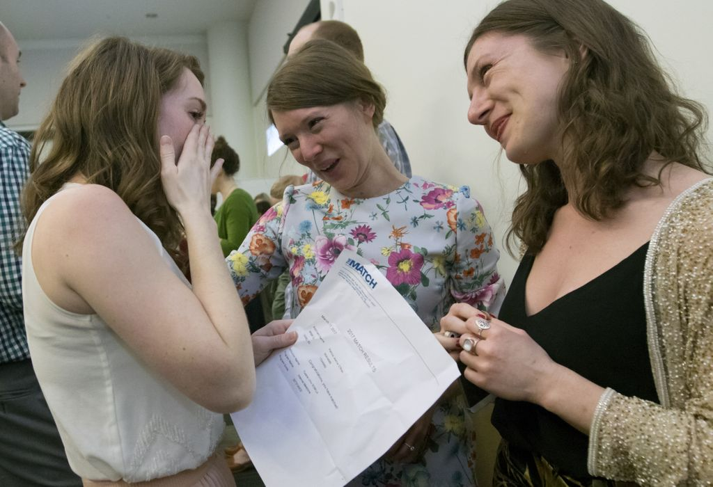 Two people congratulate a third person who is holding a paper that says match at the top.