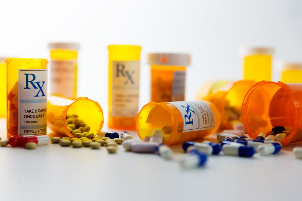 7 orange prescription bottles, several varieties of loose pills on a white surface