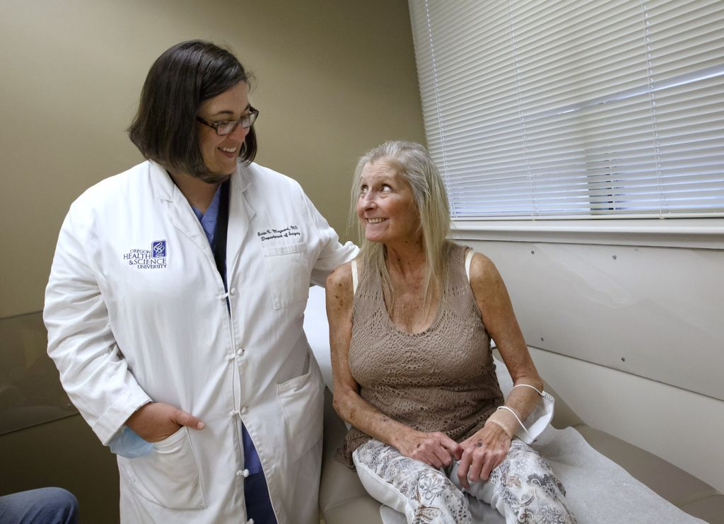 Liver donation recipient looks up at her transplant doctor, smiling