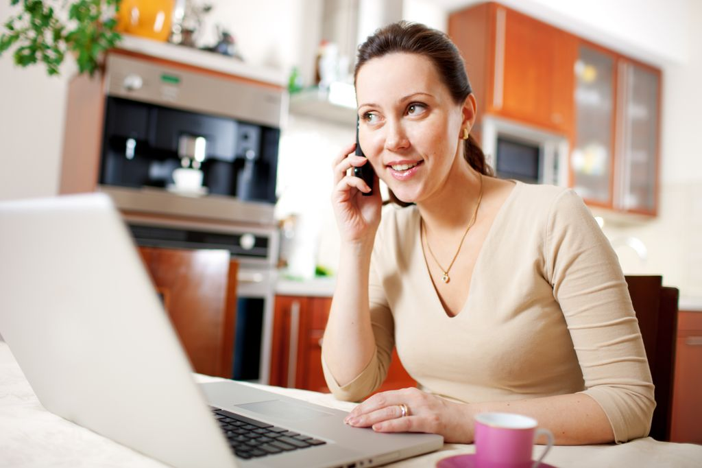 woman at desk in front of a computer, talking on a phone