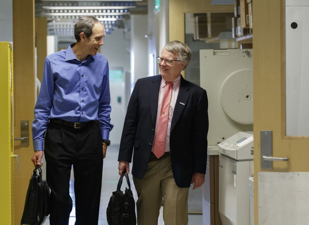 two men walking down a hallway, briefcases in hand, chatting with one another.