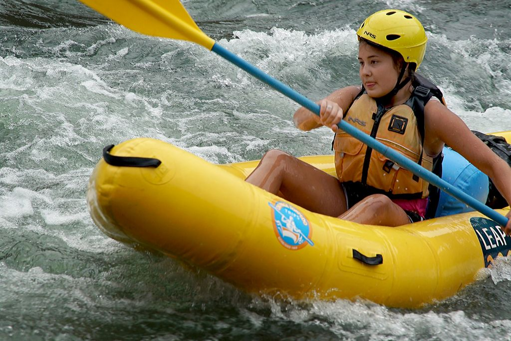 young girl paddling and inflatable kayah through whitewater rapids