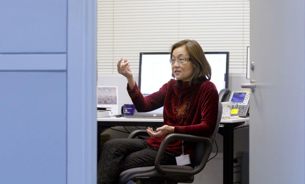Woman with dark hair, sitting at her desk, seen through the doorway