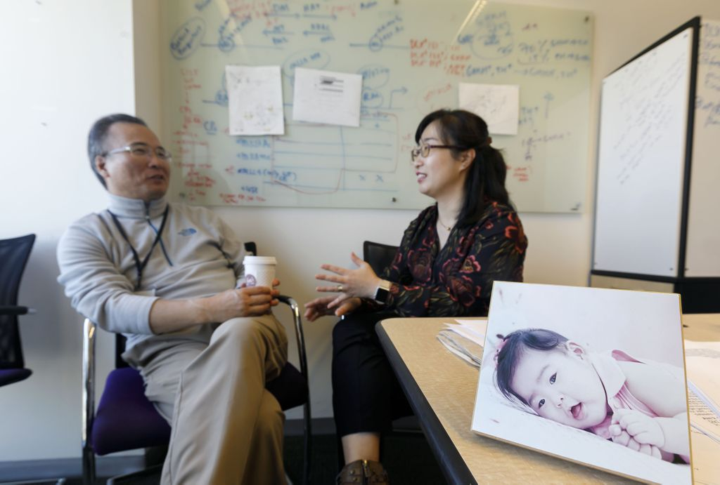 husband and wife meeting in an office, a photo of their daughter is on the desk, at the right.