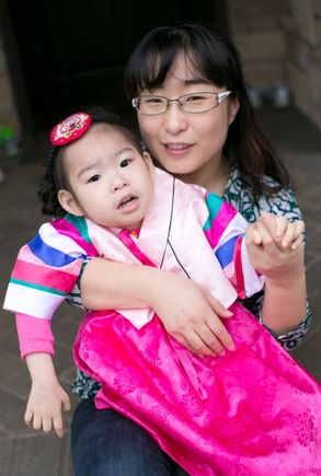 young girl in korean cultural clothing, with her mother