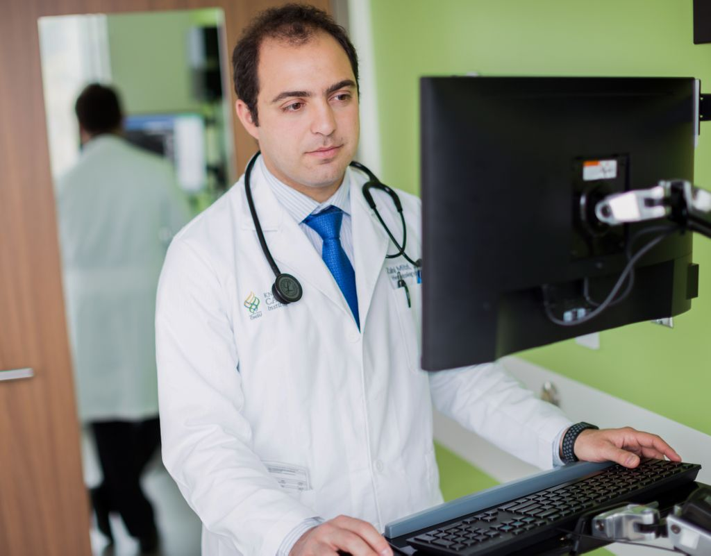 doctor, wearing white coat, with stethoscope around his neck, working on the computer