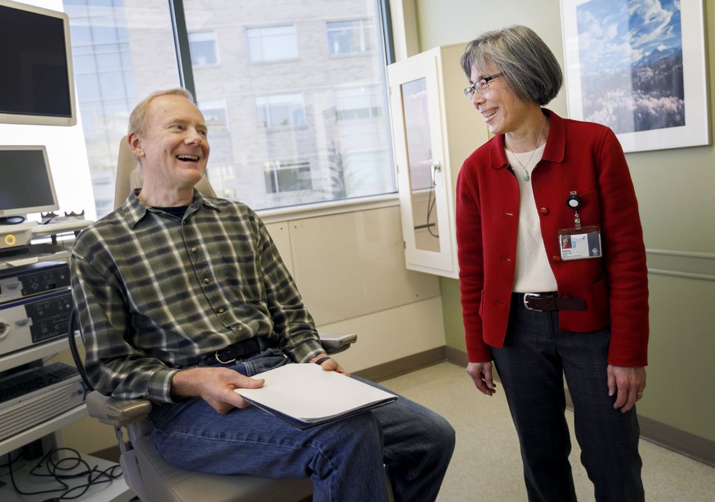 man sitting in chair, laughing with his doctor