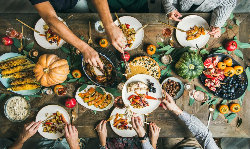 overhead shot of a table filled with holiday entrees, and people passing their plates