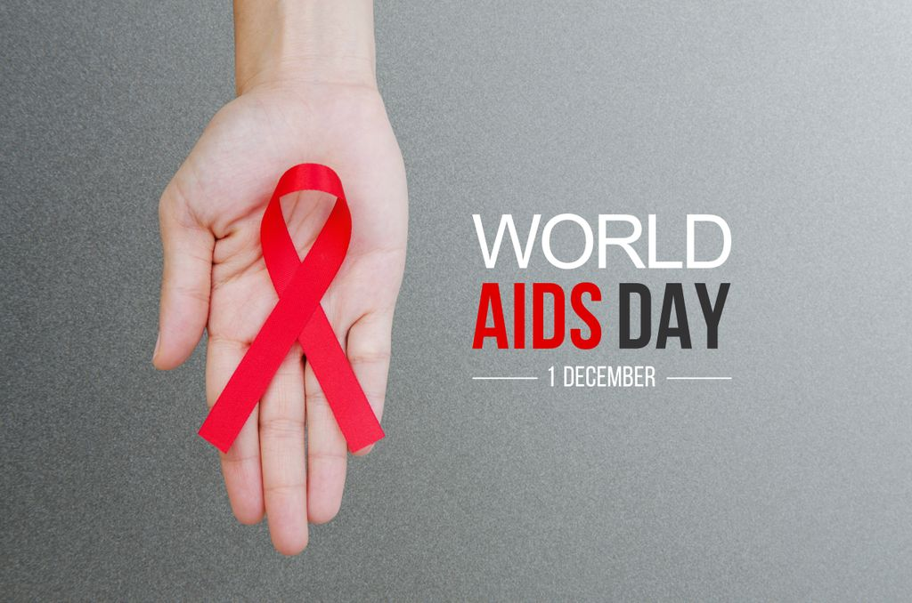 hand holding a red ribbon for World Aids day