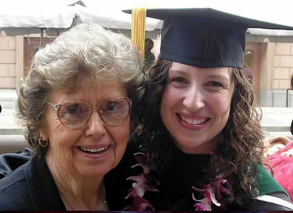 older woman with her face pressed to a younger woman's face, who is wearing a graduation cap and gown