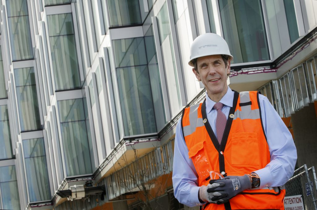 man in orange vest and hard hat standing in front of a building under construction