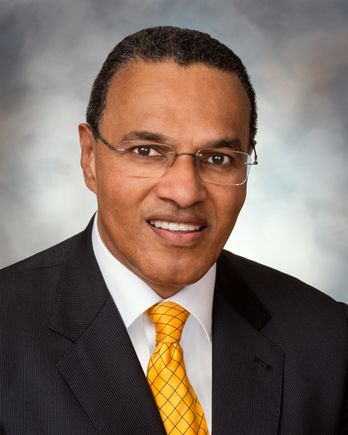 man wearing suit and site, with glasses, smiling at camera