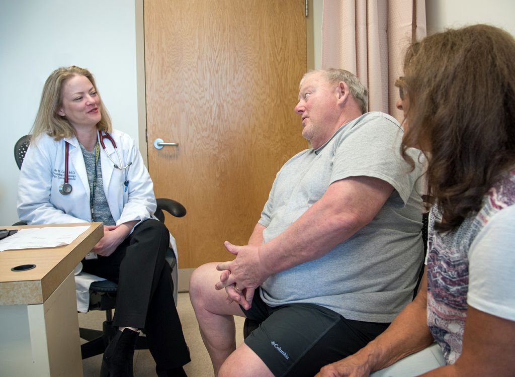 doctor on left, meeting with patient and his wife in a medical appointment
