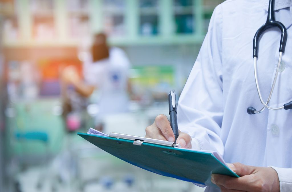 close up shot of doctor writing on a clipboard, with white coat and stethoscope on