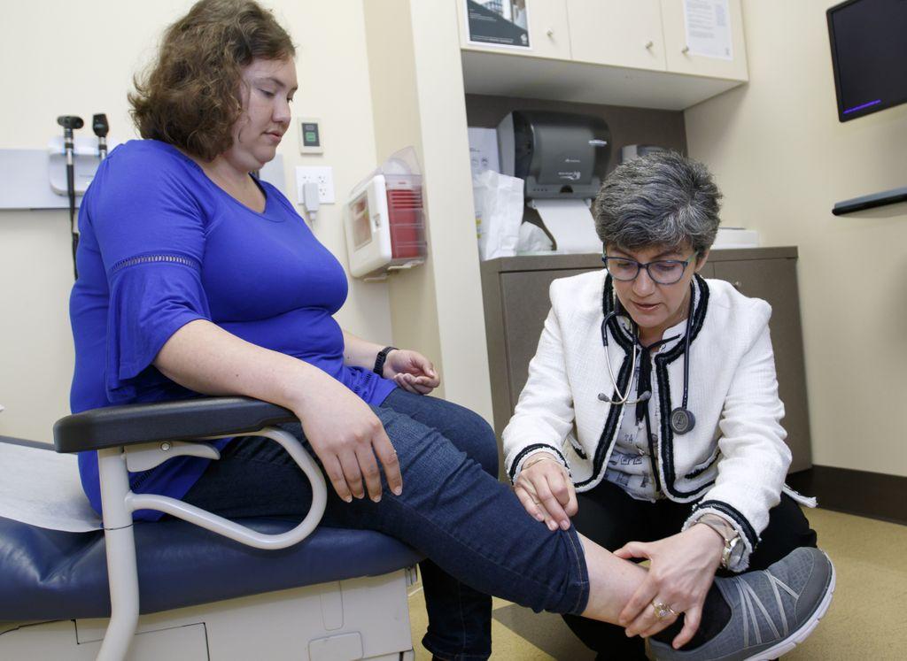 doctor examining legs of patient