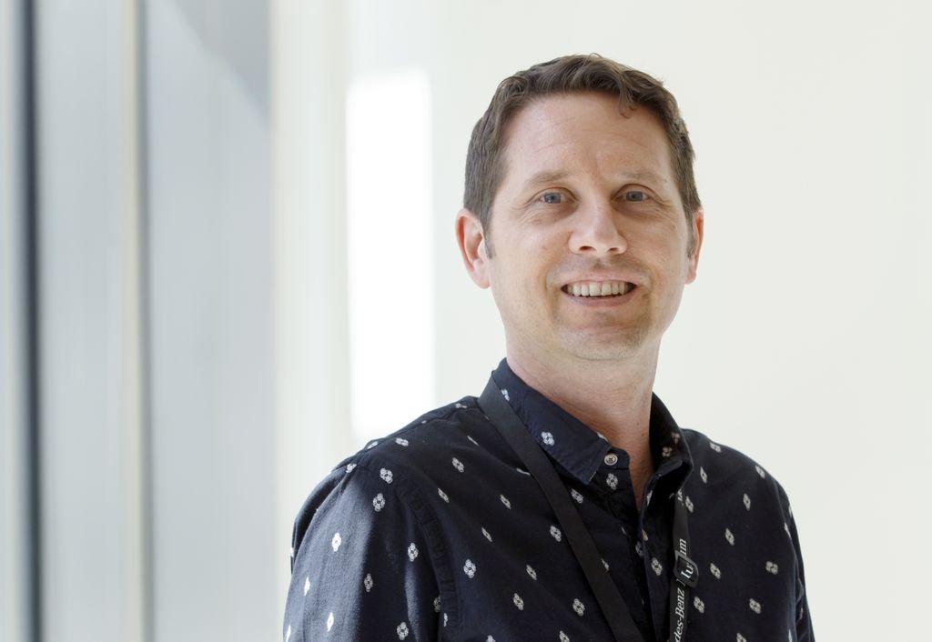 man wearing dark shirt smiling at camera