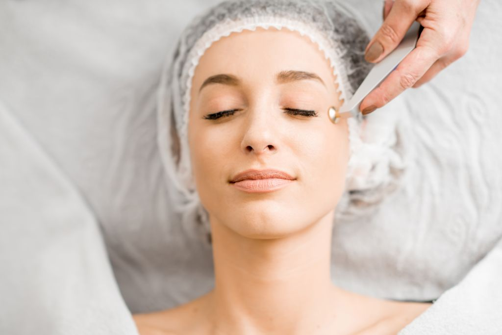 woman lying on table, hair in a cap, receiving electrolysis treatment