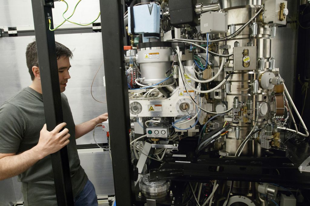 man on left side of image, looking into giant cryo-em microscope