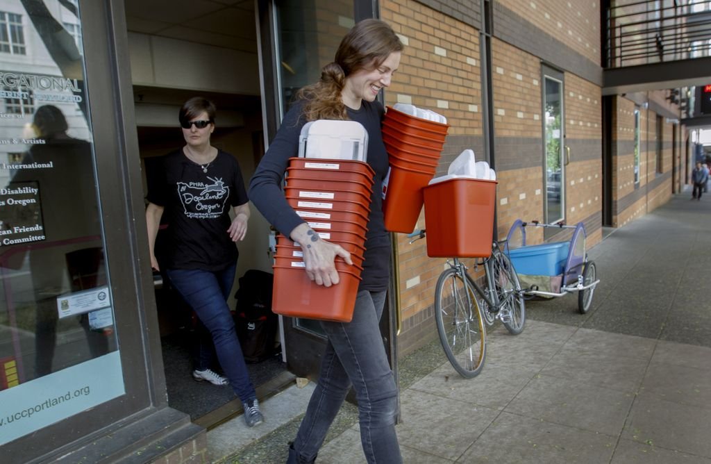 woman carrying armfuls of syringe safety boxes to load up on a bike trailer