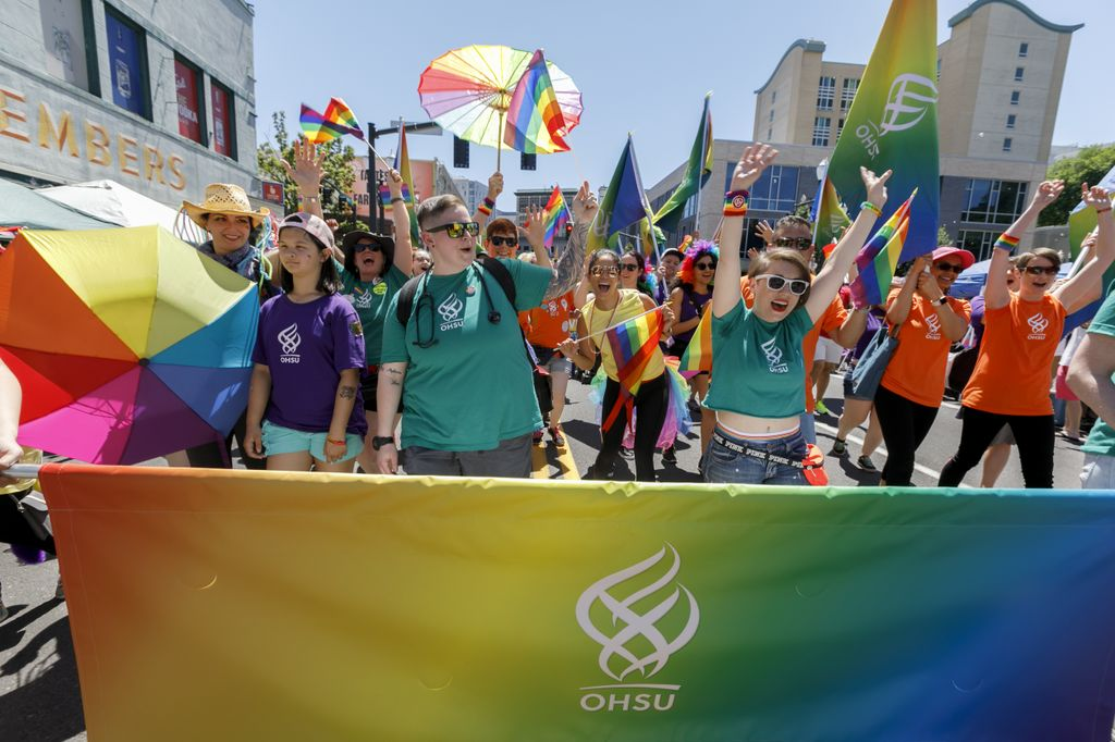 a colorful banner with OHSU logo is carried by people at the portland pride parade