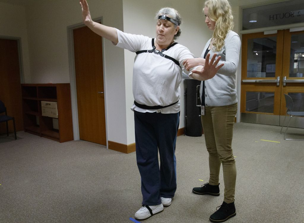 woman wearing sensors on her head, losing her balance while other woman helps stabilize her.