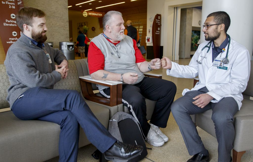 three men visiting on a couch in the lobby of the hospital