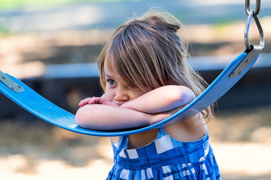 sad girl leaning on a swing