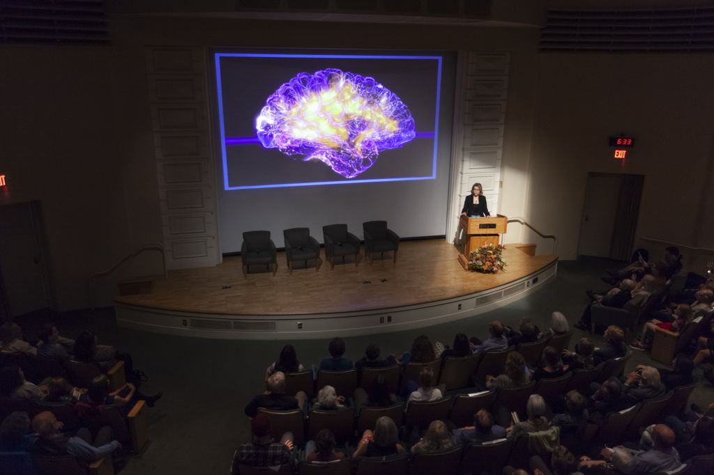 woman speaking on stage in front of a large projection of a brain