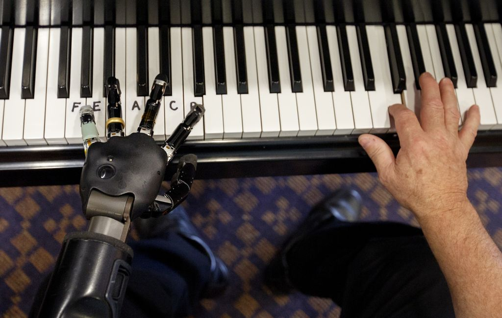 two hands on a piano keyboard, left hand is robotic